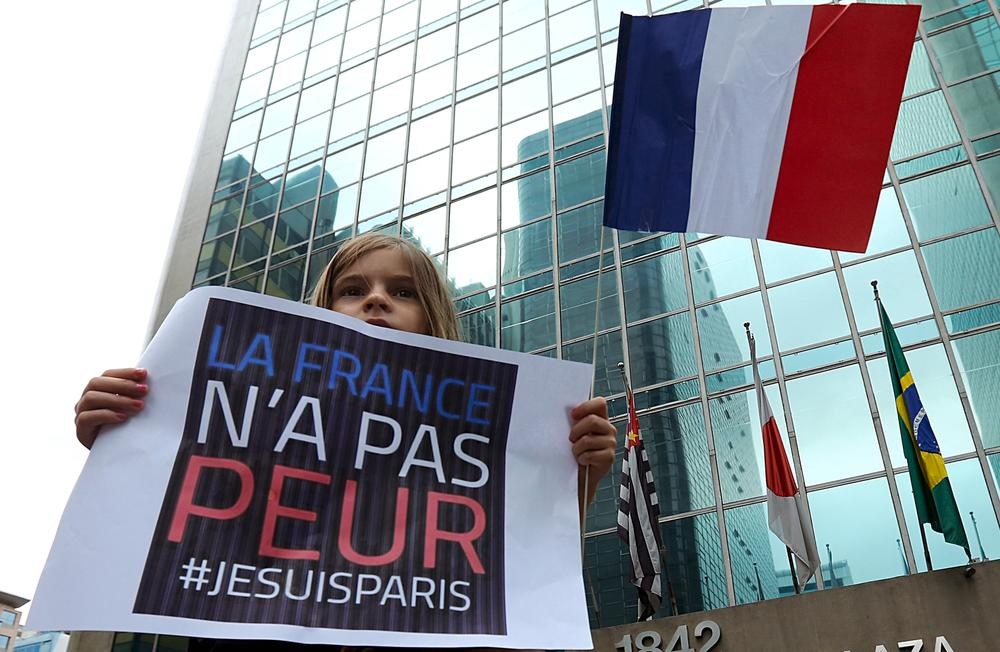 "A girl holds a sign during a vigil in tribute to the victims of the Paris attacks, in Sao Paulo, Brazil, November 15, 2015. The sign reads: ""France is not afraid. #I am Paris"". REUTERS/Rodrigo Paiva EDITORIAL USE ONLY. NO RESALES. NO ARCHIVE"